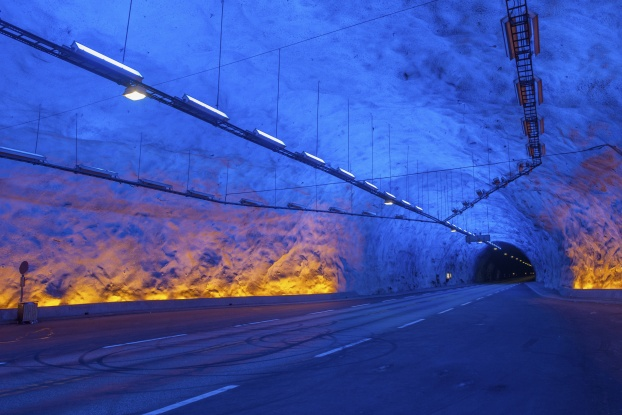 "To connect the Norwegian cities of Laerdal and Aurland highway engineers were forced to solve a small problem: the Hornsnipa and Jeronnosi mountains. Instead of going around the obstacles, they decided to go through them. The result was the Laerdal Tunnel, which runs through solid gneiss rock for 15 miles (24 kilometers), earning it the title of the world's longest completed road tunnel. Excavating such a structure is only one of the challenges. Designers also have to ensure that motorists can make the long, underground trek without succumbing to ""highway hypnosis."" To address this problem, the Norwegian Public Roads Administration called in a team of psychologists to make sure the finished roadway was as stimulating as possible. The agency recommended including blue lights and gentle curves to keep drivers engaged. They also suggested that the final tunnel be divided into four sections to help reduce monotony. Motorists entering the Laerdal Tunnel today might not notice these design enhancements, but they'll certainly appreciate them when they emerge safely into daylight after the 20-minute journey through the middle of a mountain."