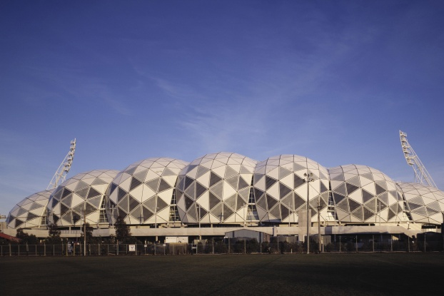 "Its name suggests a completely boring structure. After all, what could be strange or intriguing about a rectangular stadium? But when you take a bird's-eye view of AAMI Park, as it's known in Australia, you can see why the design has been hailed as the ""next generation of sports stadia"" [source: The Institution of Structural Engineers]. The most distinctive feature is the roof, which draws inspiration from the geodesic domes of American engineer R. Buckminster Fuller. To build a geodesic system, you piece together interlocking polygons to form a sphere. The resulting structure is strong, yet uses far fewer materials than something similar built with traditional construction methods. The roof of AAMI Park actually boasts several geodesic domes, packed together like a complicated soap-bubble surface. And yet the stadium still manages to use 50 percent less steel than a typical cantilever structure [source: Major Projects Victoria]. It also contains significant amounts of recycled building material, collects rainwater from the roof and minimizes power use with an advanced building-automation system. When it opened in May 2010, it collected a number of awards for architectural innovation, structural engineering excellence and eco-friendly construction techniques. But don't expect to hear the cheers of environmentalists. The stadium holds more than 30,000 spectators, who can get more than a little rowdy cheering for local soccer and rugby teams."