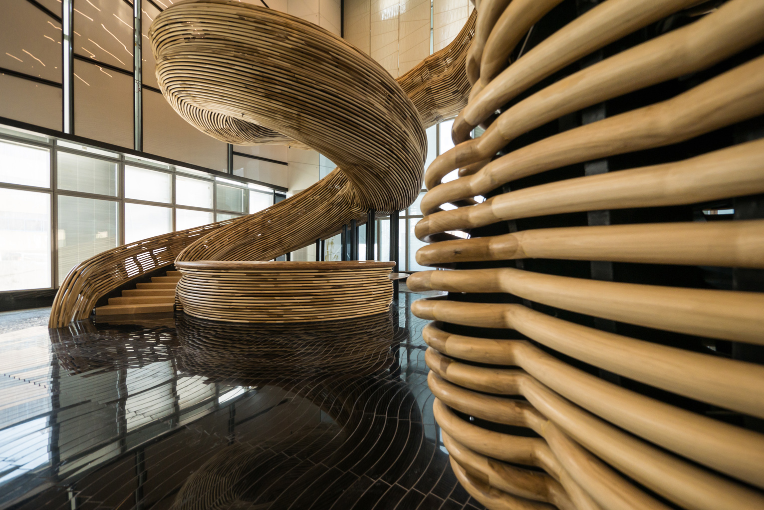 3a. Photography by ITAY SIKOLSKI - The reception desk was conceived as the starting point for the spiraling wooden sculpture, completed with the same wooden profiles as the railings