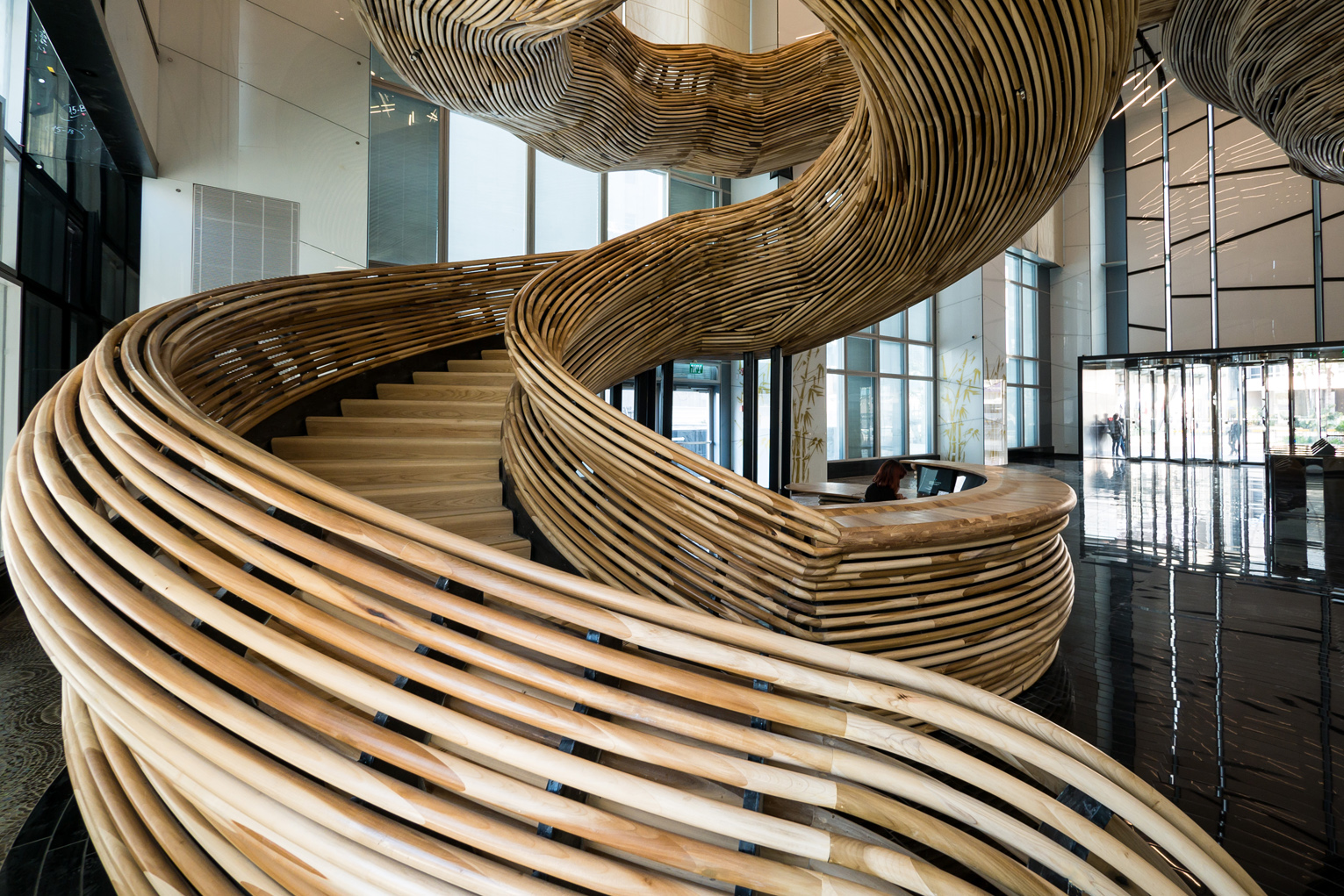 3b. Photography by ITAY SIKOLSKI - The reception desk was conceived as the starting point for the spiraling wooden sculpture, completed with the same wooden profiles as the railings